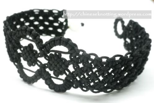 Knotted with black cord. Tied with a shell bead as a button.15.5cm long and about 2 cm wide.